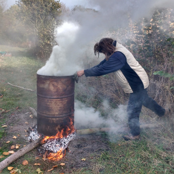 Making charcoal in an oil drum kiln